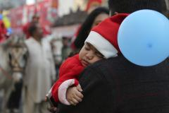 A child dressed in a Santa costume sleeps during a procession to celebrate Christmas